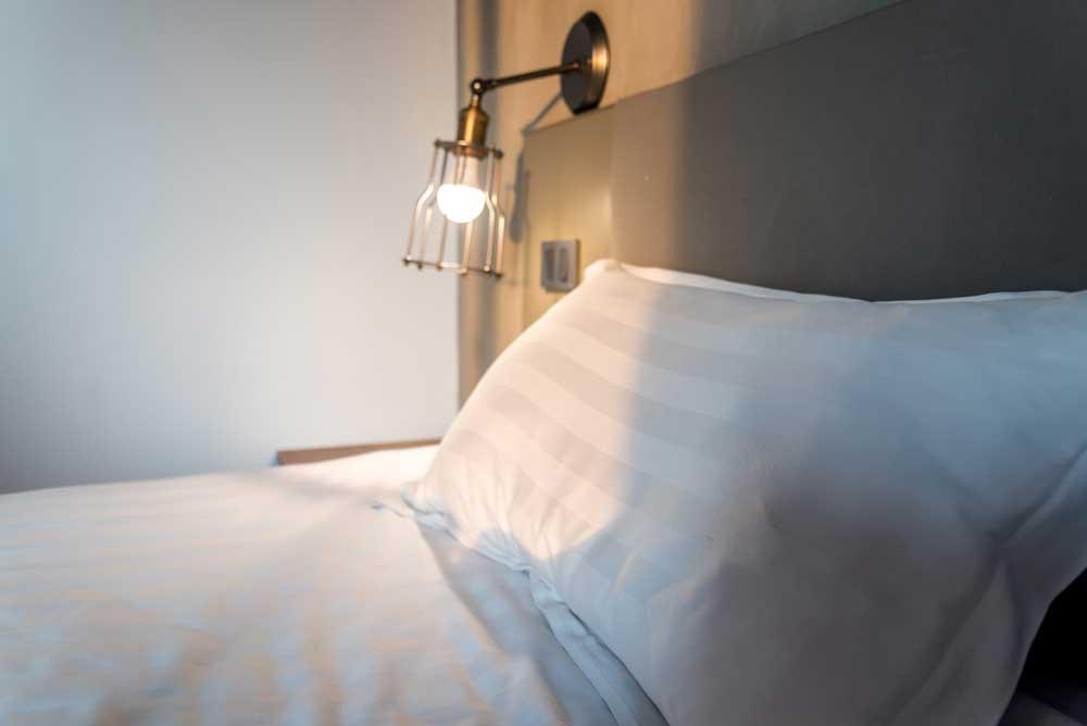 Onmisbaar: een mooie wandlamp naast het bed
